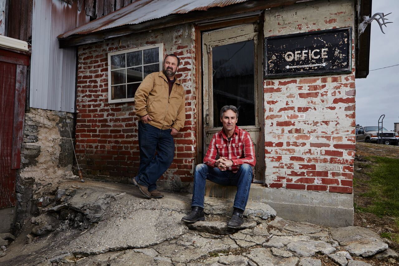 Mike and Frank, stars of the television series AMERICAN PICKERS, sit in front of a brick building
