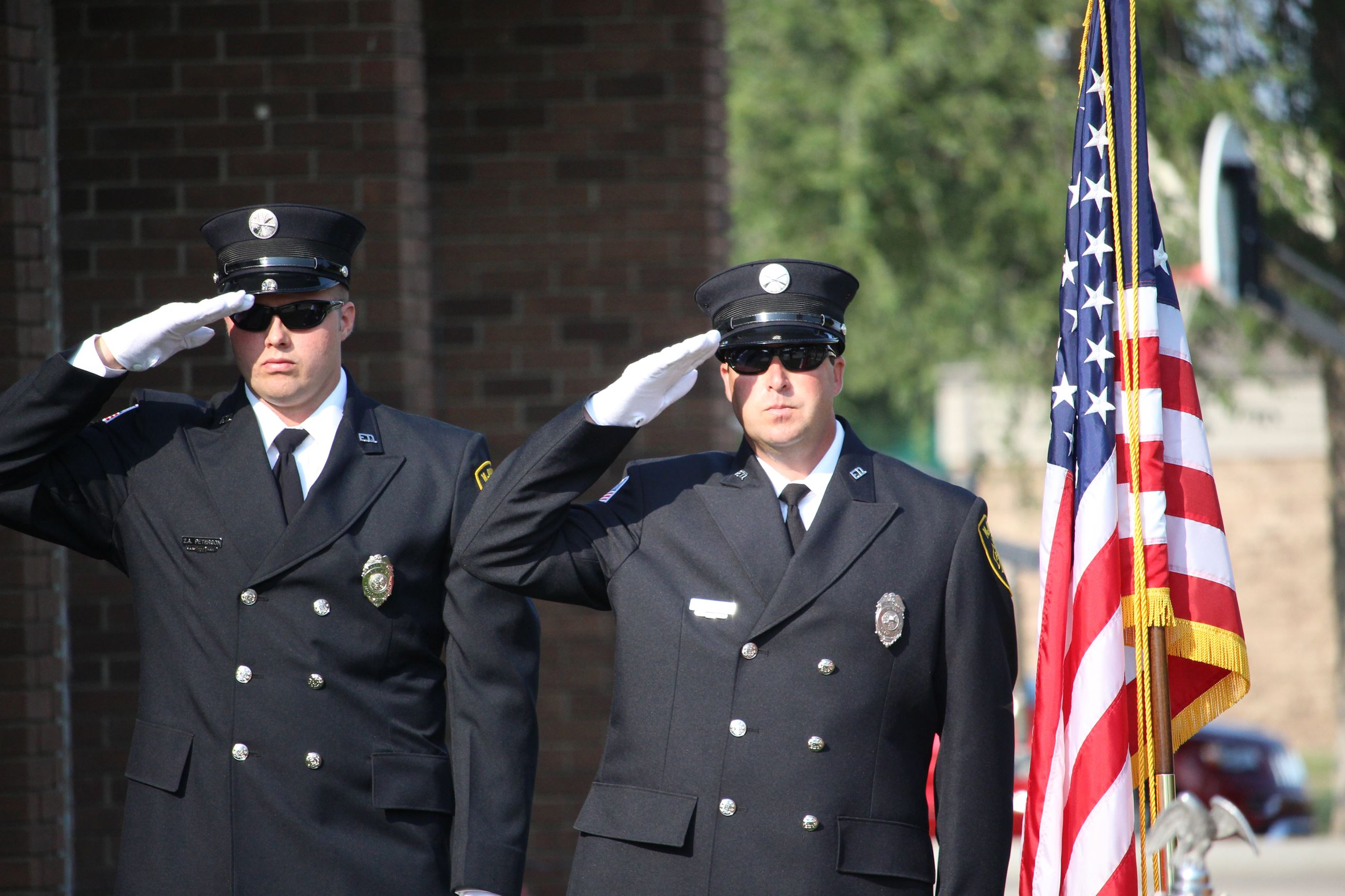 Two uniformed firefighters salute the American flag