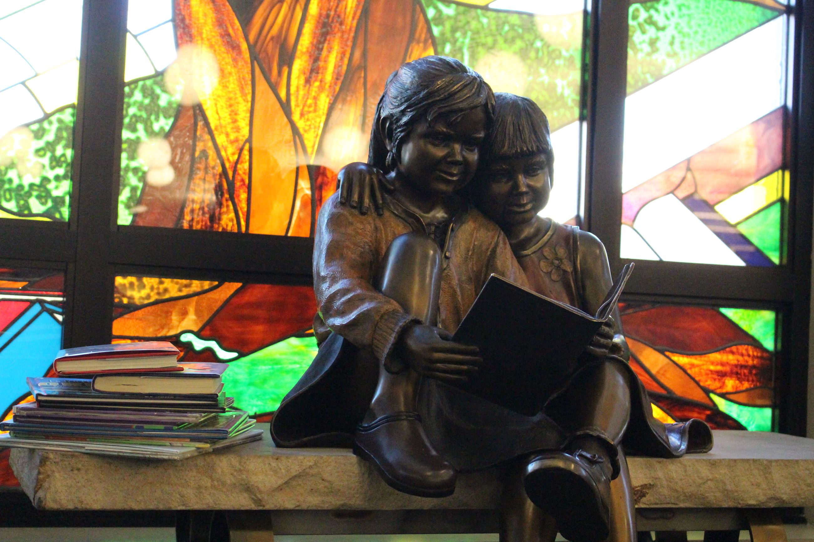 Bronze statue of little boy and girl reading a book while sitting on a bench