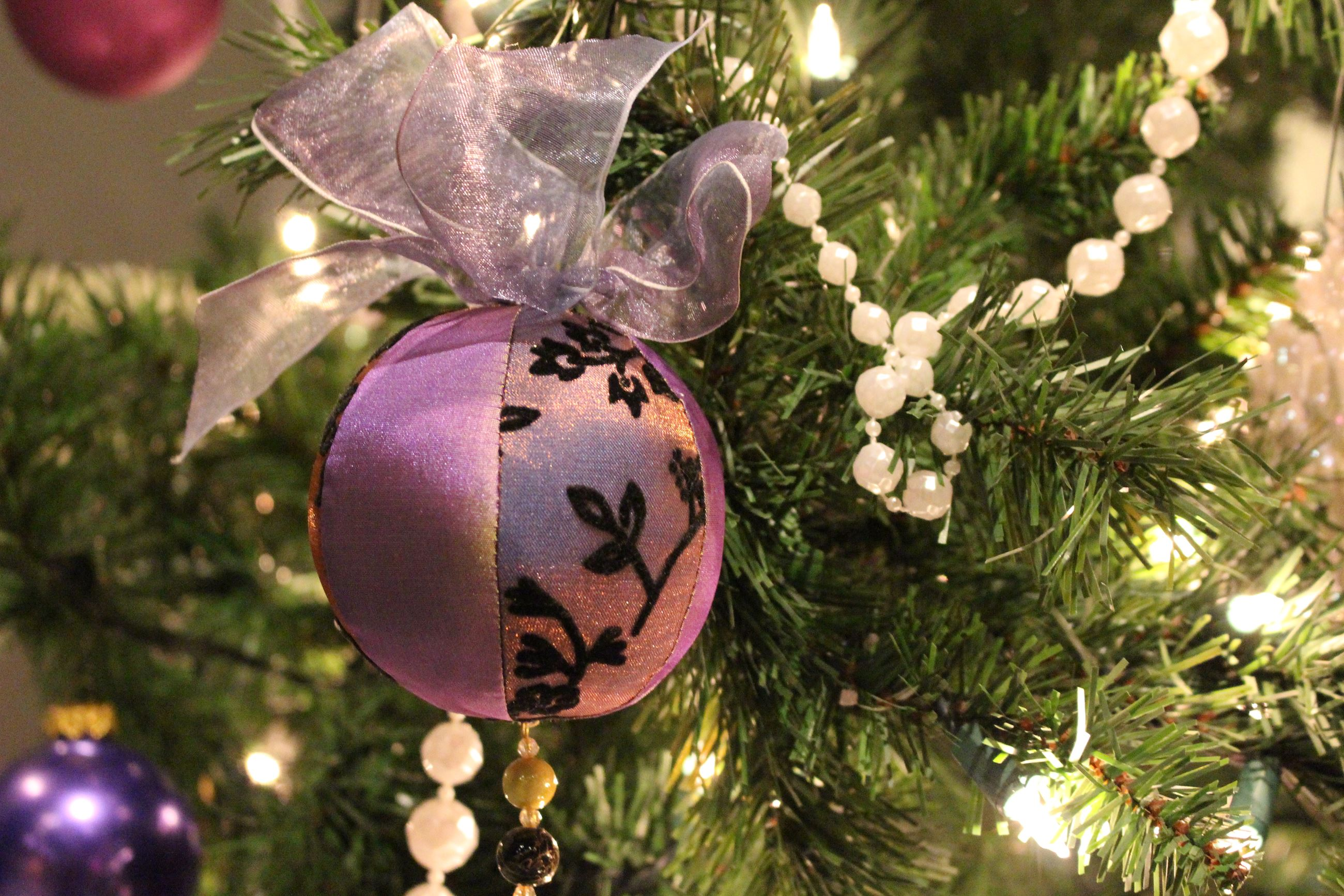 Round purple ornament hanging on a Christmas tree with white beads
