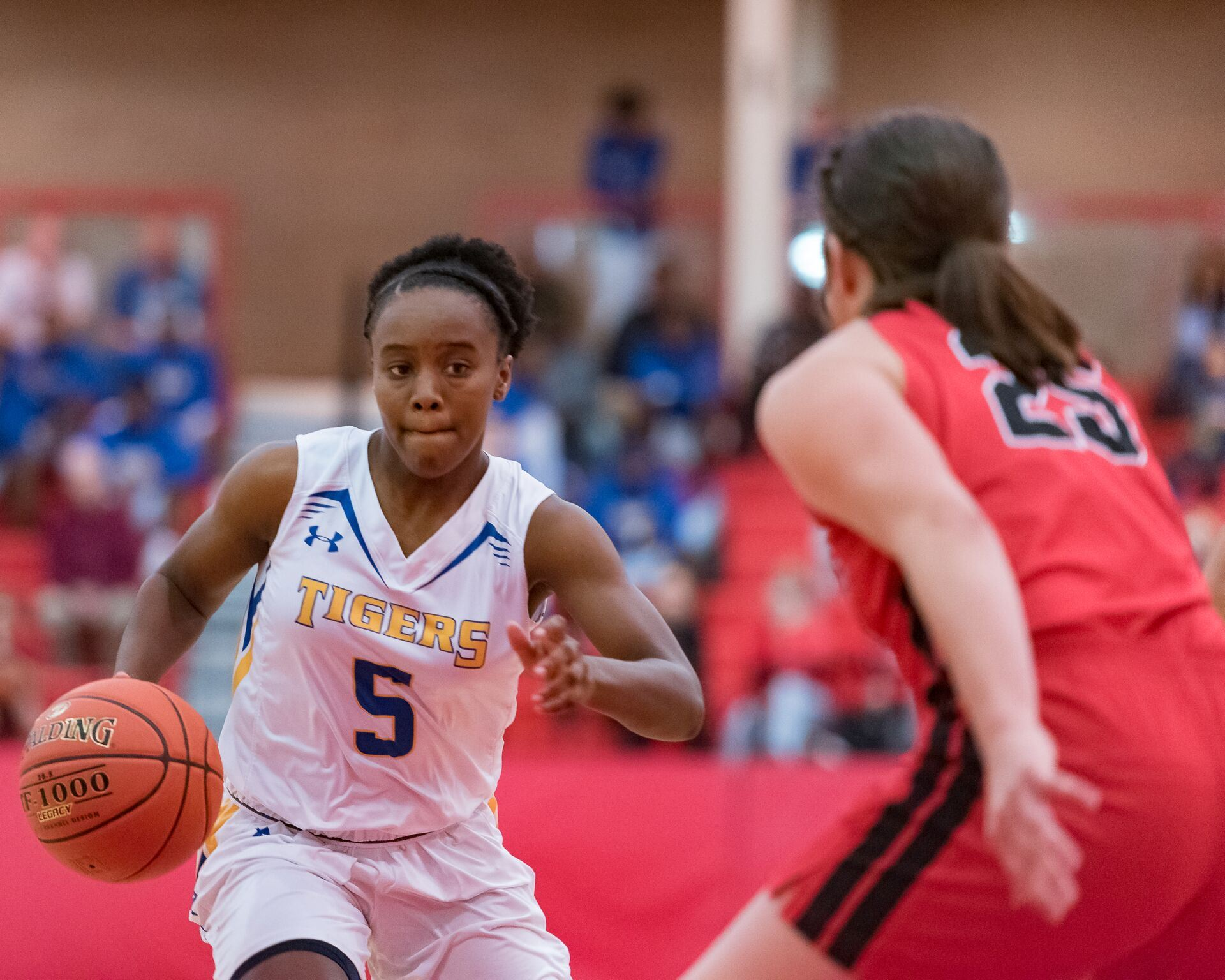 Black women wearing a white uniform playing basketball against white woman wearing a red uniform