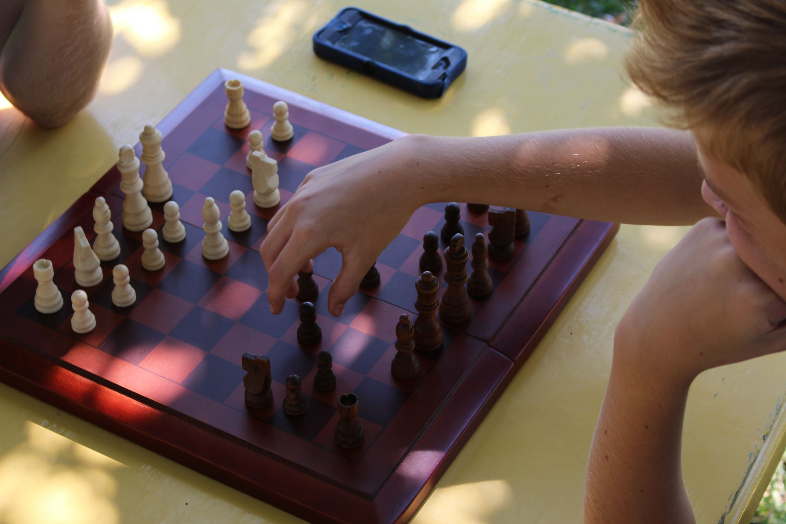 Image of hand hovering over a chess board pondering the next move