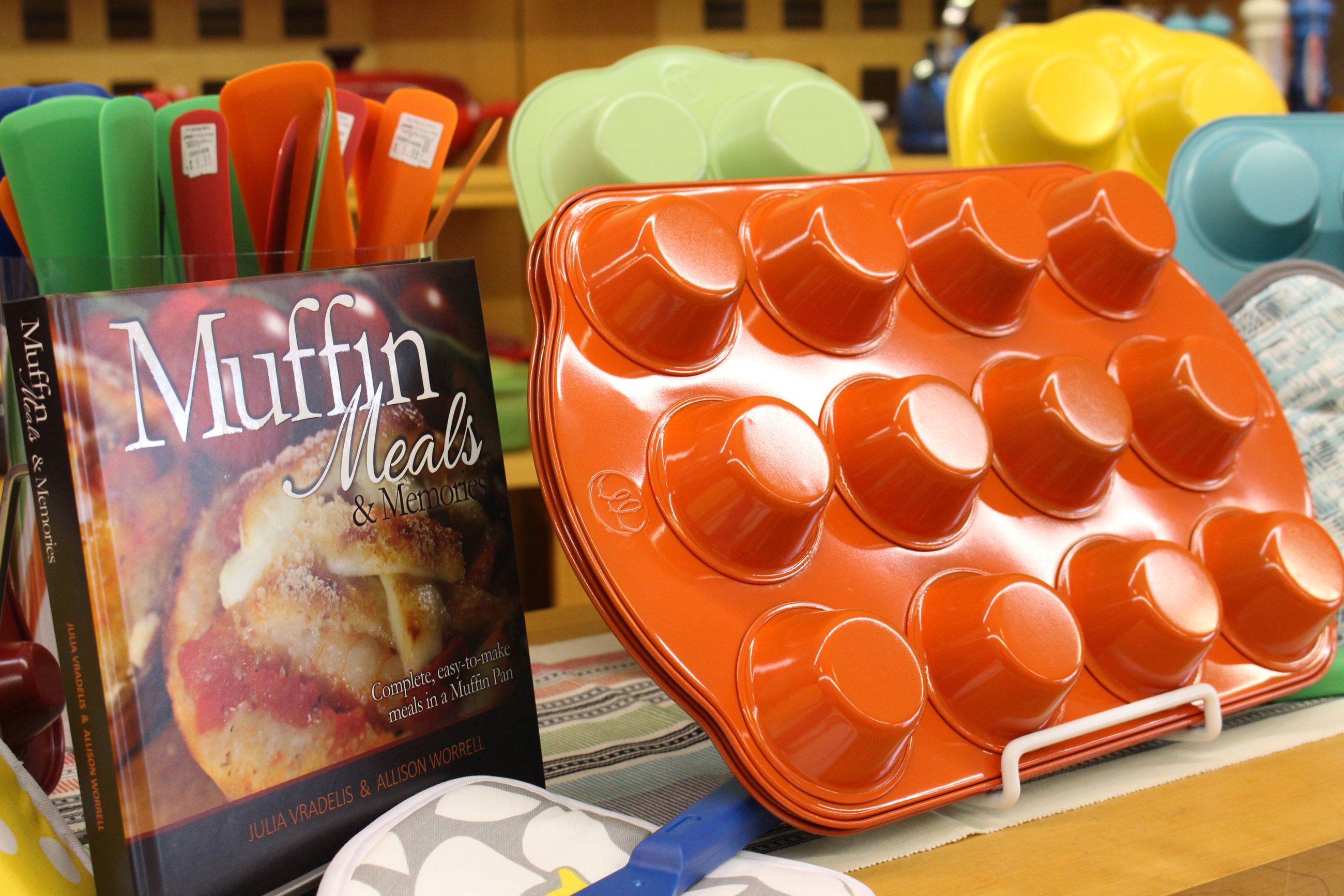 Orange muffin tin placed next to a muffin cookbook