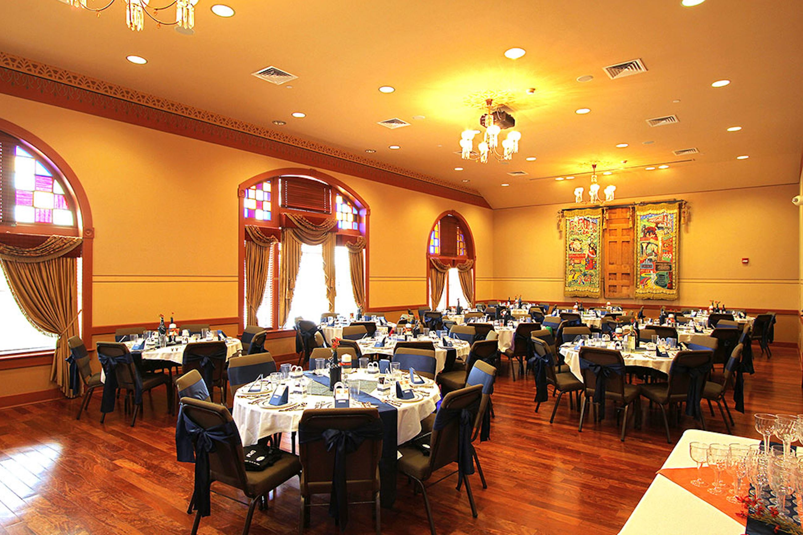 Historic ballroom with tall windows and wooden floor with tables set for a fancy meal