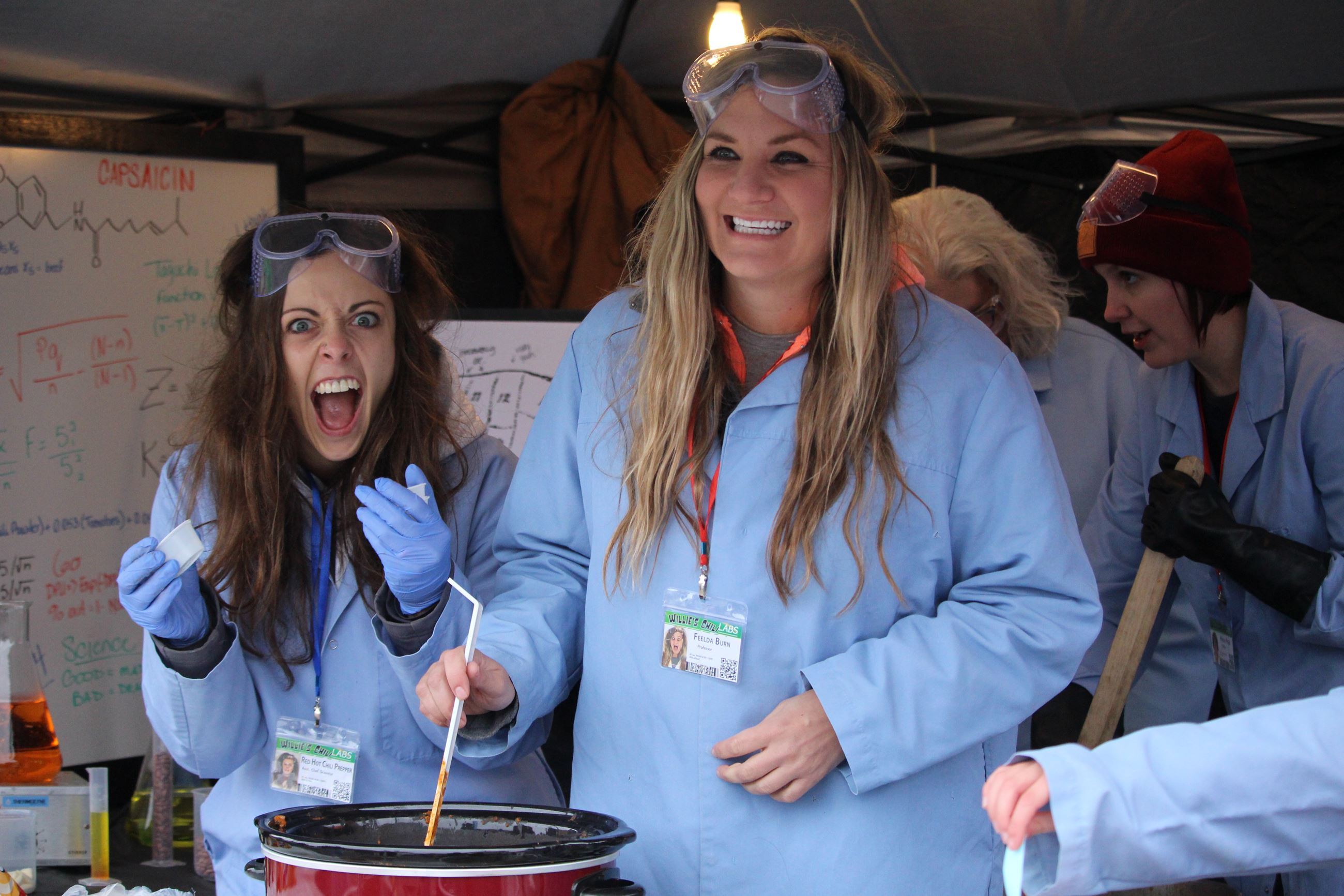 Two ladies dressed as mad scientist serve chili during a community event