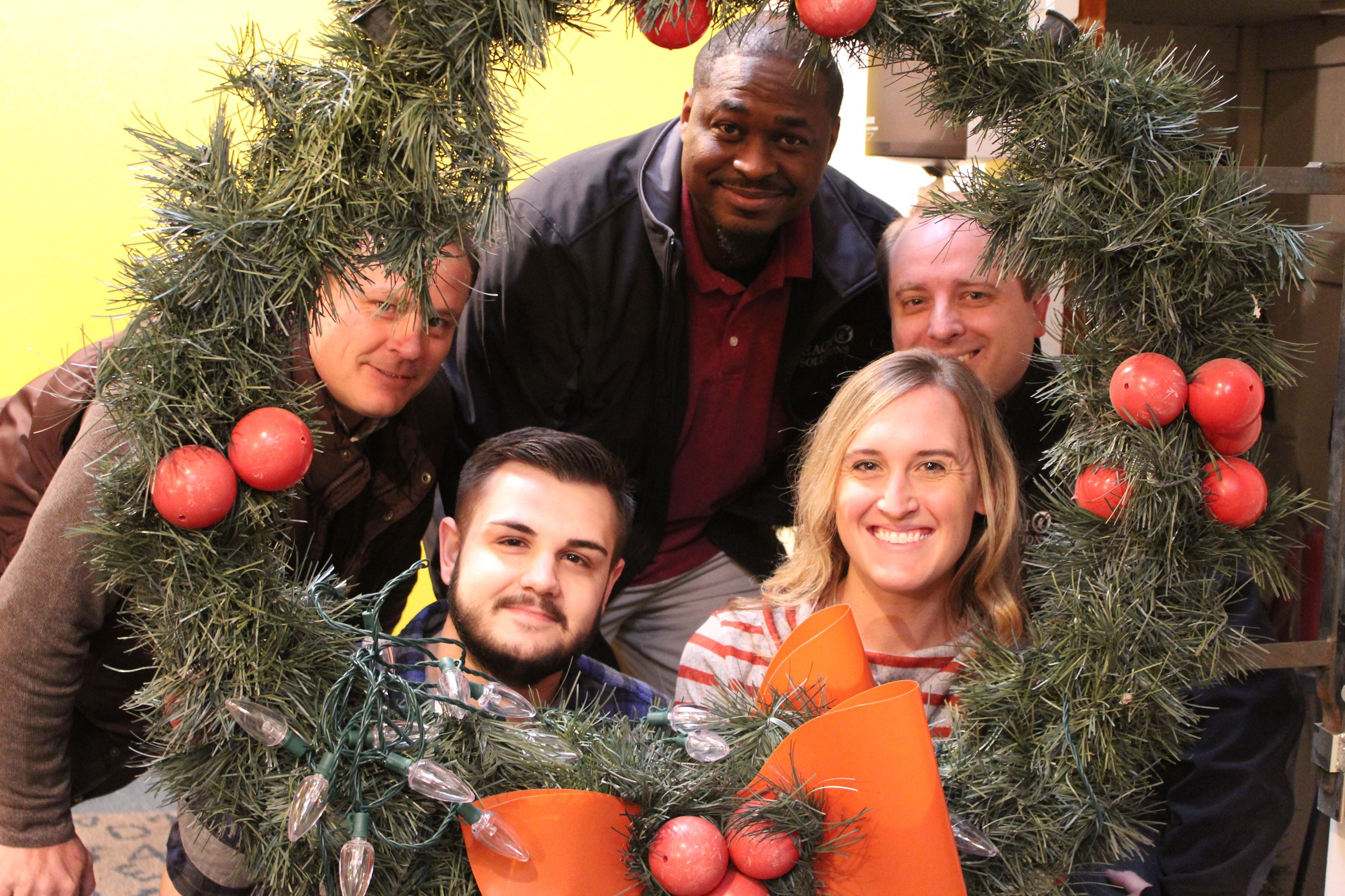 Five business representatives pose with a giant Christmas wreath