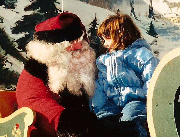 Girl in a blue coat sitting on Santa&#39s lap.