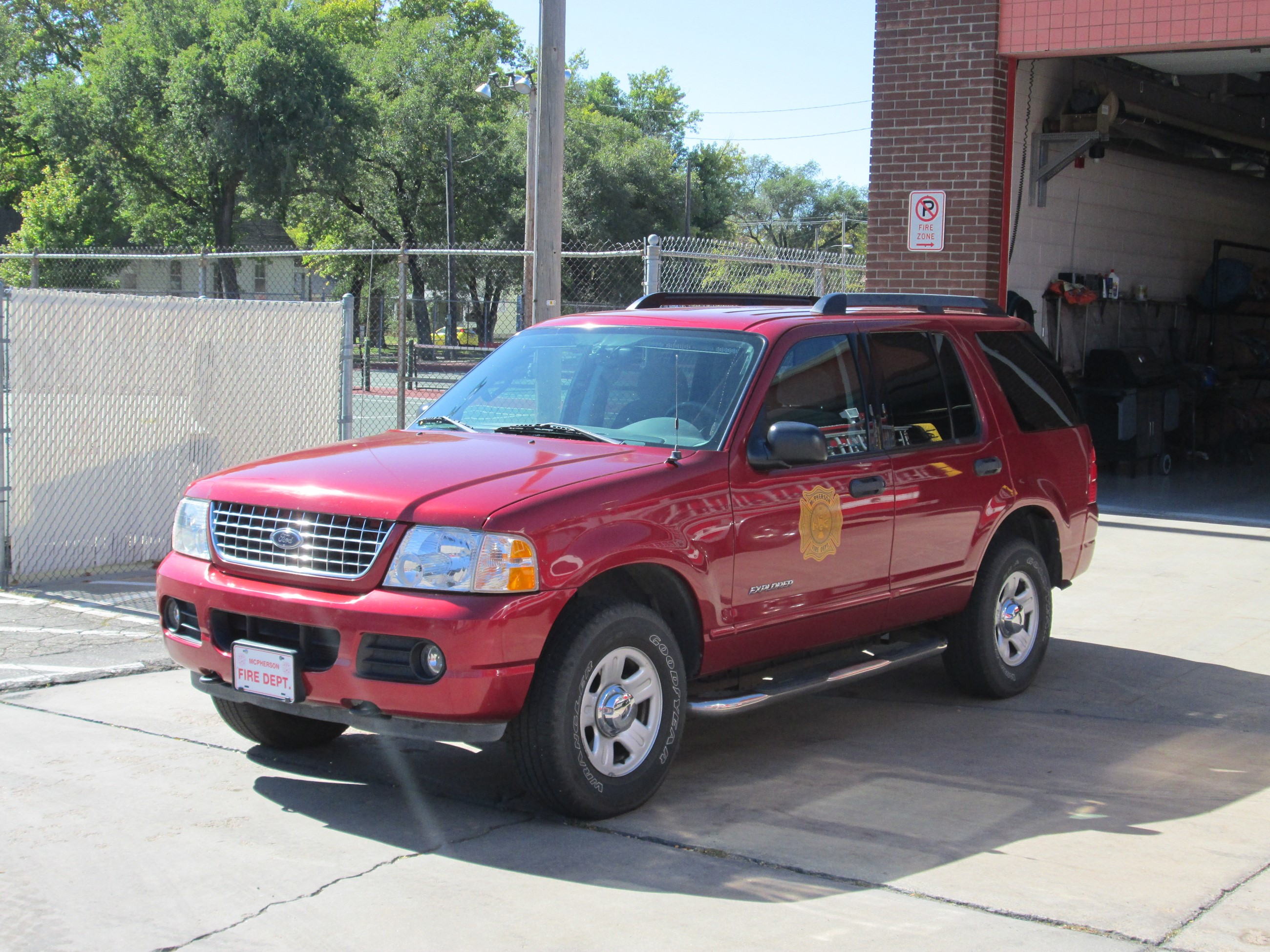Red sports utility vehicle with Fire Department logo on the side.
