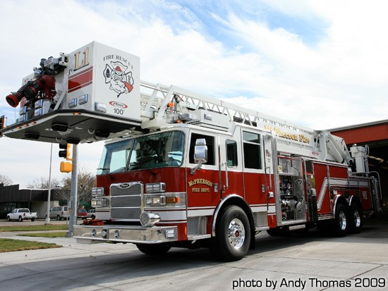 Red and white fire engine, with a large ladder on top.